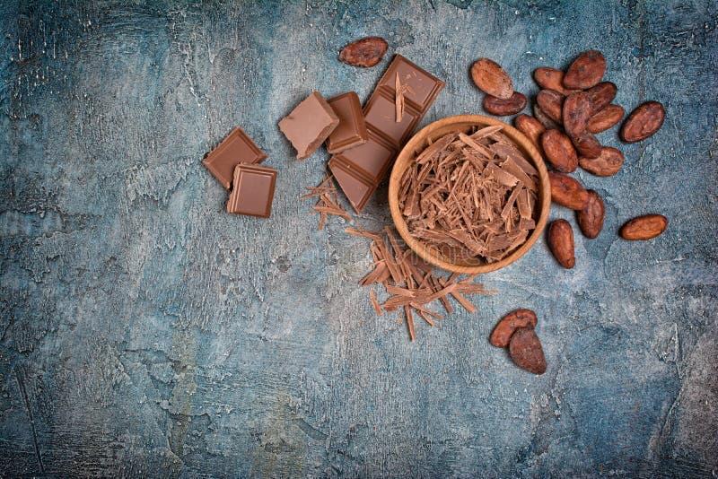 Vista superior de los microprocesadores de chocolate y de los pedazos de barras con los granos de cacao para la confitería imagen de archivo