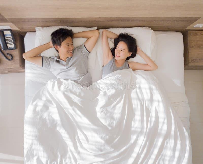 Vista superior de los pares asiáticos felices que sonríen, y durmiendo junto en cama en concepto del amor y del sexo en un dormit fotos de archivo
