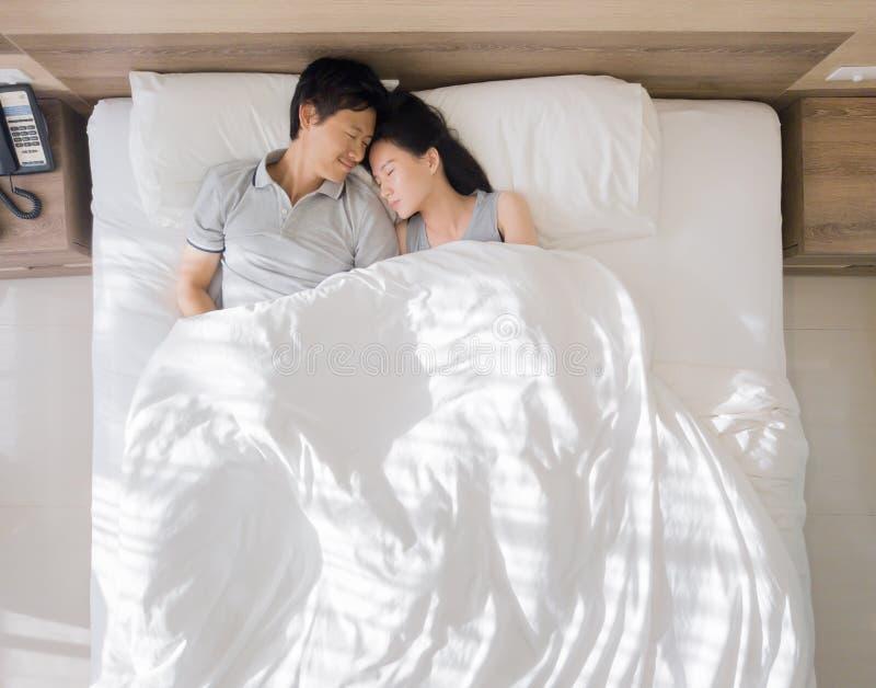 Vista superior de los pares asiáticos felices que sonríen, y durmiendo junto en cama en concepto del amor y del sexo en un dormit imagen de archivo libre de regalías