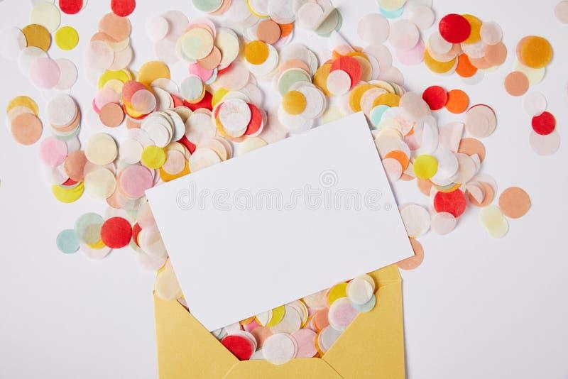 vista superior de los pedazos del confeti, del Libro Blanco y del sobre amarillo en la superficie blanca fotografía de archivo libre de regalías