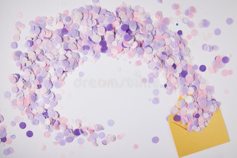 vista superior de los pedazos violetas del confeti y del sobre amarillo en superficie foto de archivo libre de regalías