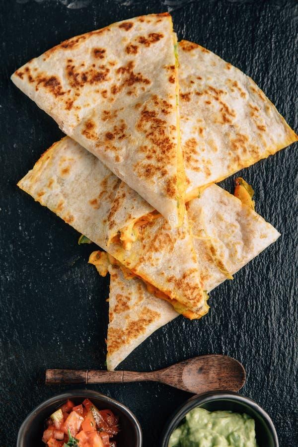 Vista superior de los Quesadillas del pollo y del queso Baked servidos con salsa y Guacamole en la placa de piedra imagen de archivo