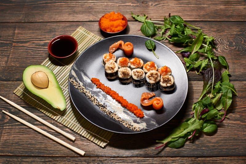 Vista superior de los rollos de sushi japoneses apetitosos en placa negra grande, sirviendo con las rebanadas de pescados, salsas fotografía de archivo libre de regalías