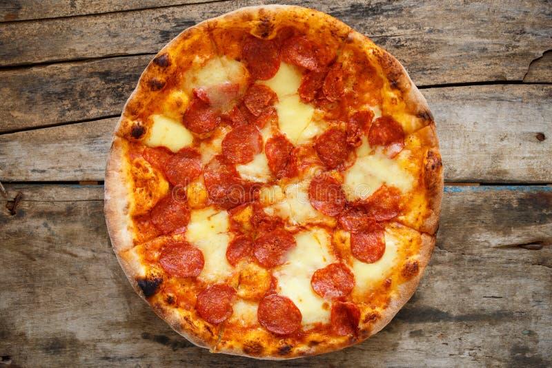 Vista superior de los salchichones de la pizza en fondo de madera imagen de archivo libre de regalías