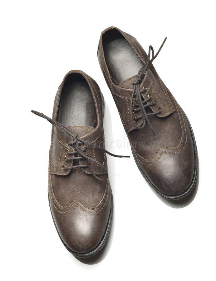 Vista superior de los zapatos de cuero marrón oscuro en el fondo blanco foto de archivo