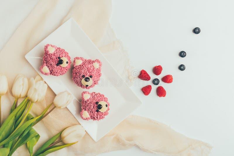 vista superior de molletes deliciosos en la forma de osos, de bayas frescas y del tulipán imagen de archivo libre de regalías