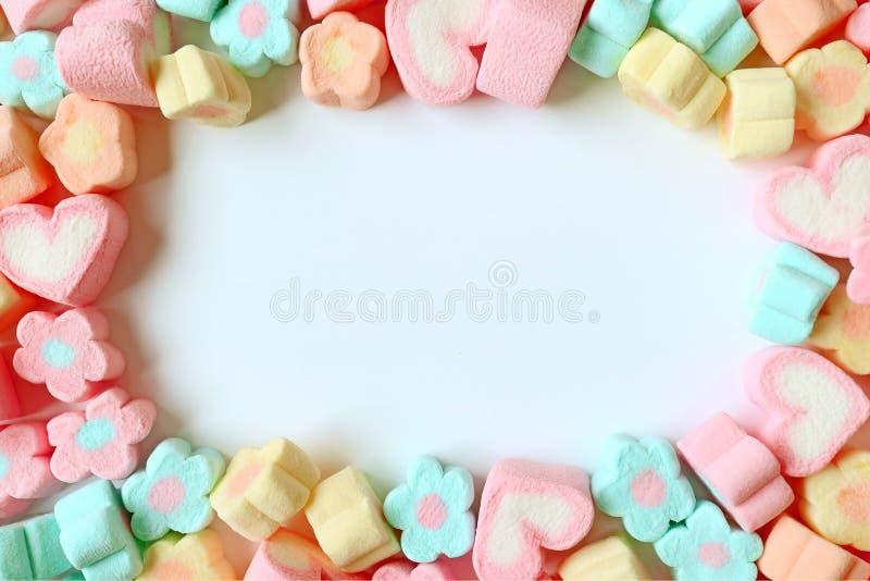 Vista superior de muchos caramelos formados y en forma de corazón de la flor del color en colores pastel de la melcocha con el es fotos de archivo