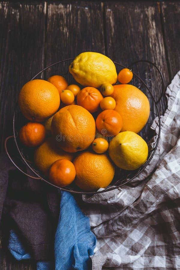 vista superior de naranjas, de mandarinas, de limones, de kumquats en placa y de toallas de cocina fotografía de archivo