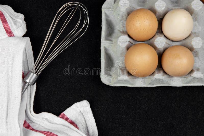 Vista superior de ovos da galinha em uma caixa da caixa e em um eggbeater em um fundo preto foto de stock