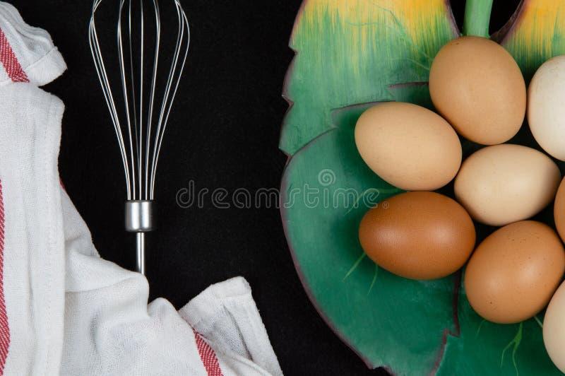 Vista superior de ovos da galinha em uma placa foliforme e em um eggbeater em um fundo preto imagem de stock royalty free