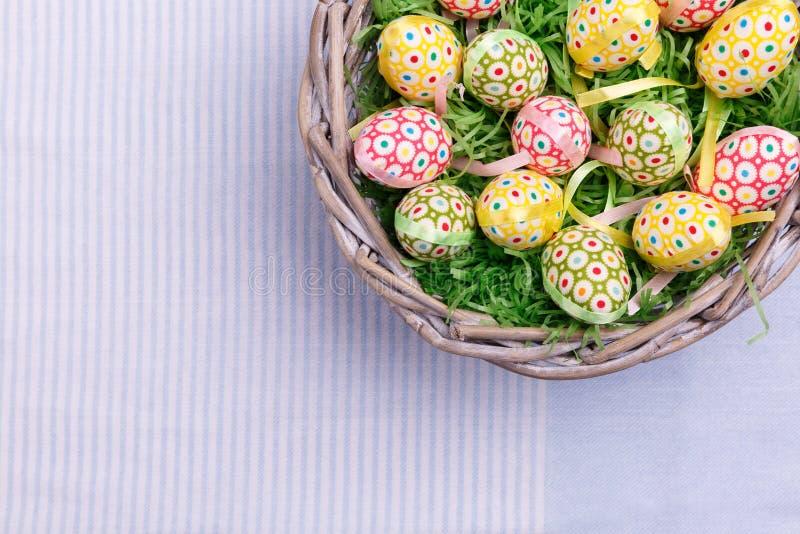 Vista superior de ovos e de penas de codorniz da Páscoa em uma cesta de vime, close-up Cartão de cumprimentos de Easter fotografia de stock