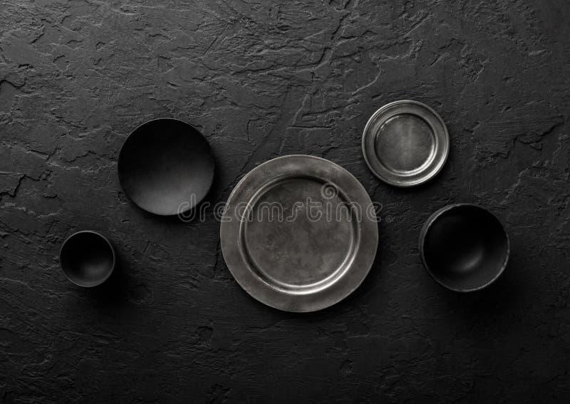 Vista superior de placas y de cuencos vacíos negros y grises en fondo de piedra negro fotos de archivo libres de regalías