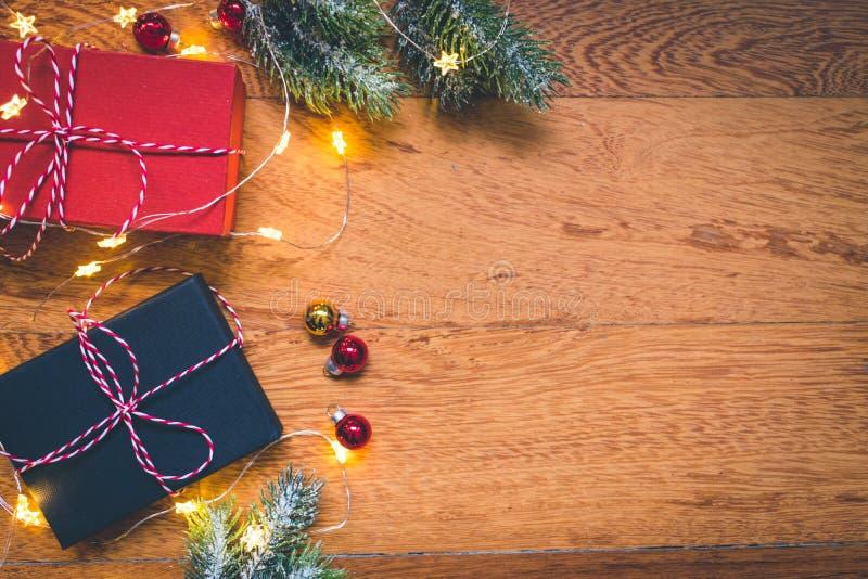 Vista superior de presentes, de ramas de árbol de pino, de bolas de la Navidad y de luces en fondo de madera imagen de archivo