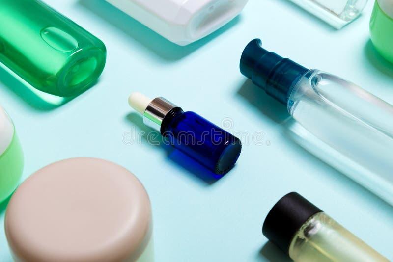 Vista superior de productos cosméticos en diversos tarros y botellas en fondo azul Primer de envases con el espacio de la copia fotografía de archivo