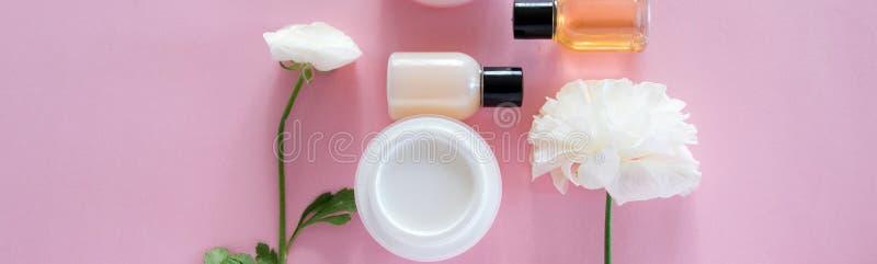 Vista superior de productos cosm?ticos y de flores delicadas en fondo rosado Tratamiento de la belleza de la salud fotos de archivo libres de regalías