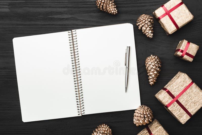 Vista superior, superior, de regalos de Navidad en un fondo rústico negro de madera, cuaderno de notas fotografía de archivo libre de regalías