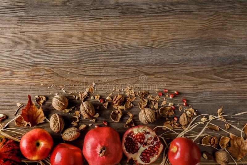 vista superior de romã, de maçãs e de nozes orgânicas no tabletop de madeira fotografia de stock royalty free