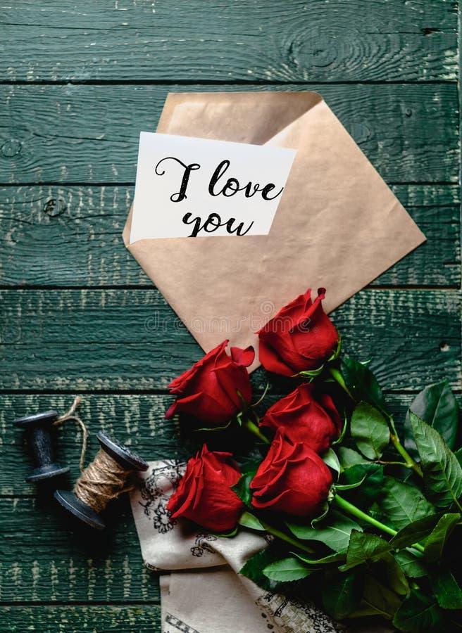 vista superior de rosas rojas y del sobre con te amo la tarjeta de la tarjeta del día de San Valentín imágenes de archivo libres de regalías