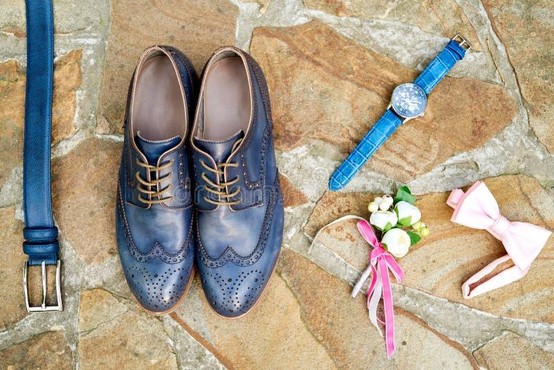 Vista superior de sapatas de couro azuis do noivo, relógios, correia, boutonniere, bowtie cor-de-rosa na pedra natural marrom Ace imagem de stock royalty free