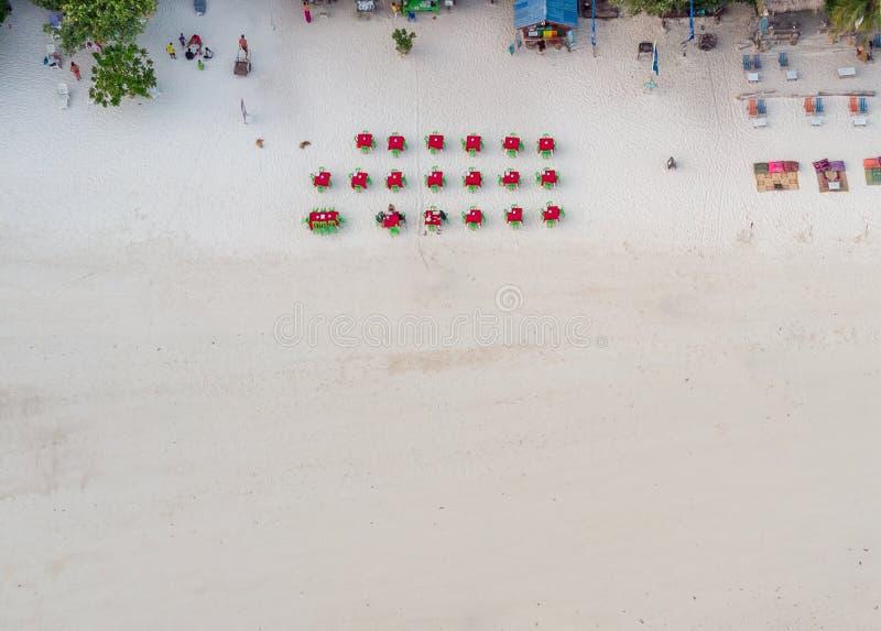 Vista superior de tablas rojas y de sillas verdes en la playa blanca en el restaurante foto de archivo