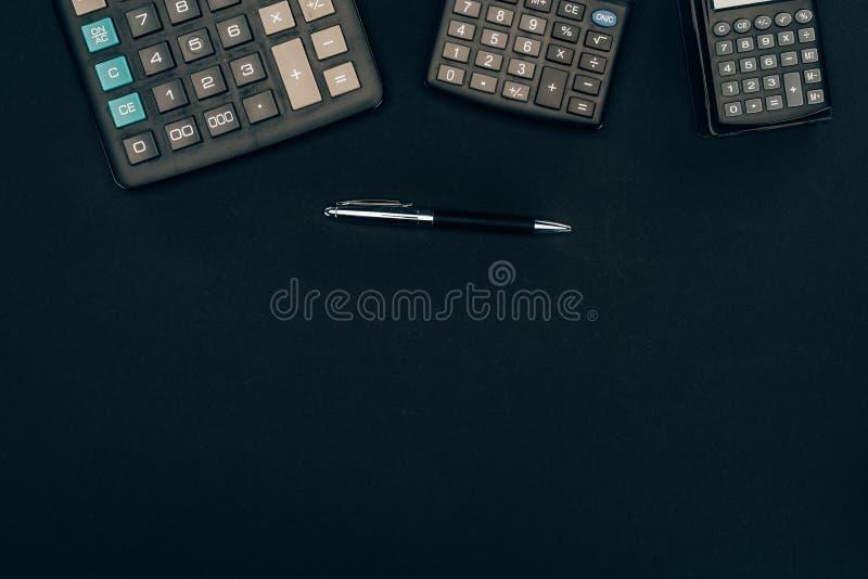 vista superior de três calculadoras de tamanhos diferentes e de pena foto de stock