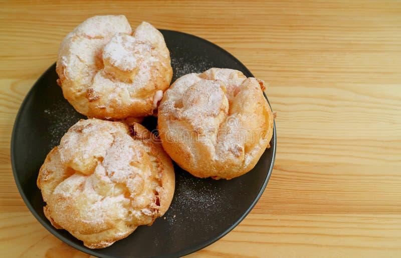 Vista superior de três Choux pastelarias de uma nata do la ou sopros de creme franceses em uma placa preta servida na tabela de m imagem de stock royalty free