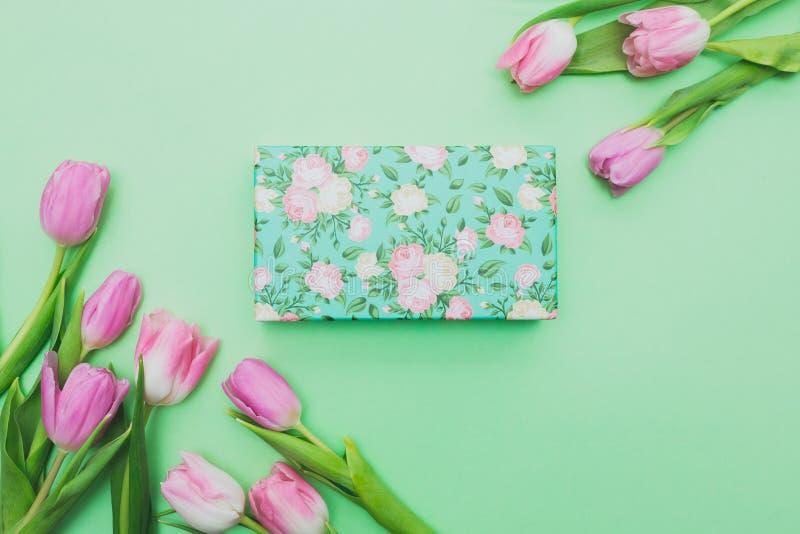 Vista superior de tulipas e da caixa de presente cor-de-rosa na luz - fundo verde com espaço da cópia imagem de stock