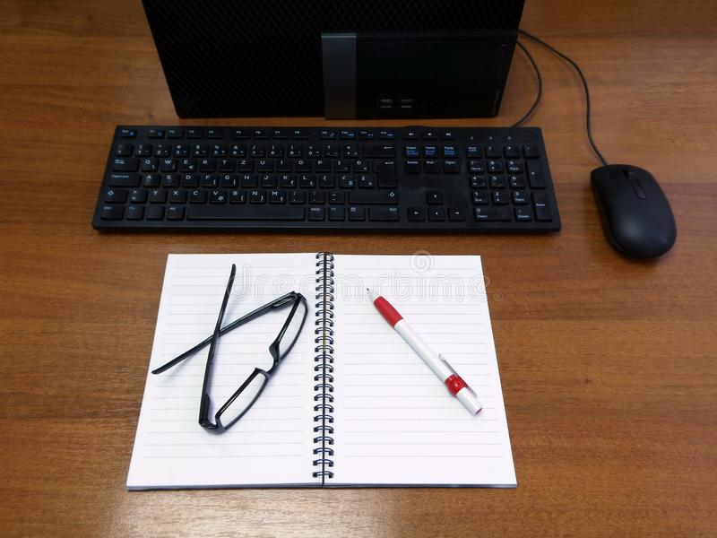 Vista superior de um computador, de um teclado, de um rato, de um caderno, de uns monóculos e de uma pena da mesa de escritório fotos de stock royalty free