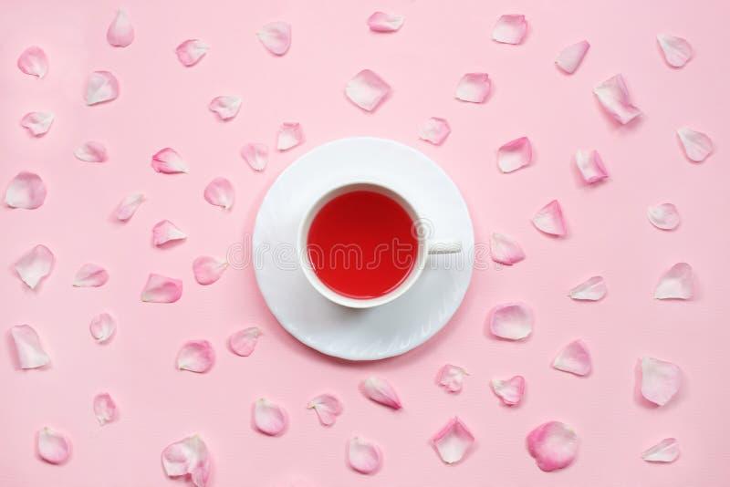 A vista superior de um copo do chá cercado pelo rosa bonito aumentou as pétalas no fundo cor-de-rosa pastel Configura??o lisa Ain imagens de stock royalty free