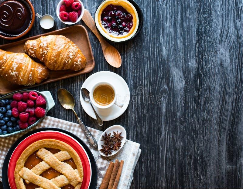 Vista superior de uma tabela de madeira completamente dos bolos, frutos, café, biscoitos fotos de stock