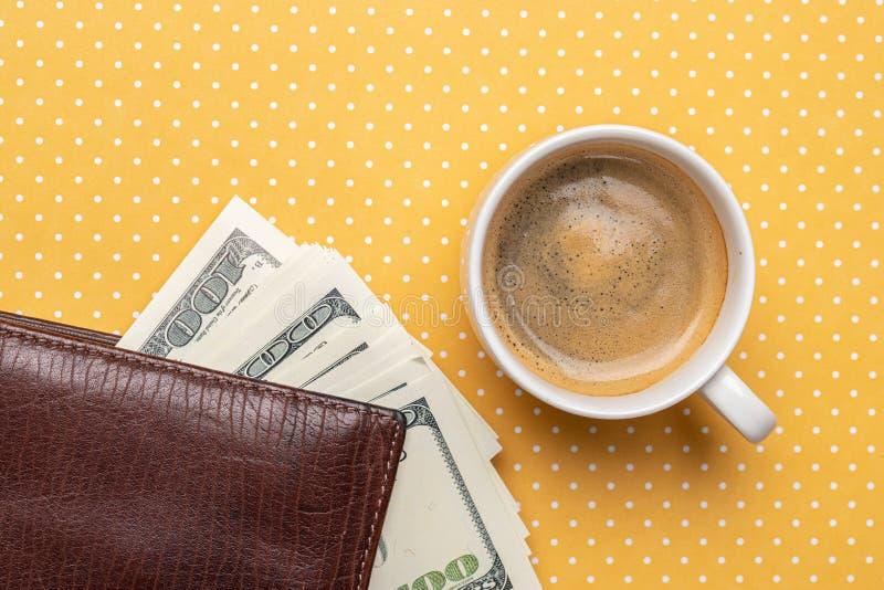 Vista superior de uma xícara de café e de uma pilha de notas de dólar em uma bolsa foto de stock royalty free
