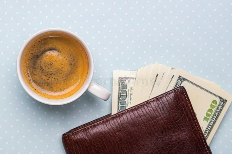 Vista superior de uma xícara de café e de uma pilha de notas de dólar em uma bolsa imagens de stock royalty free