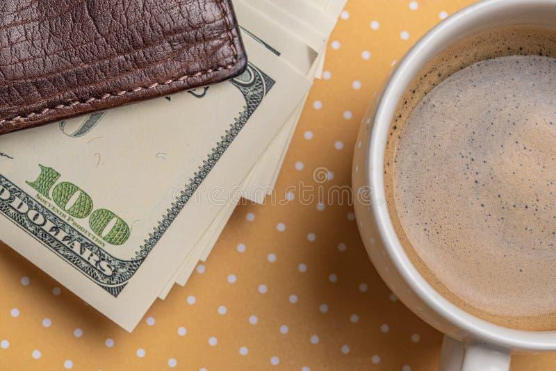 Vista superior de uma xícara de café e de uma pilha de notas de dólar em uma bolsa imagem de stock
