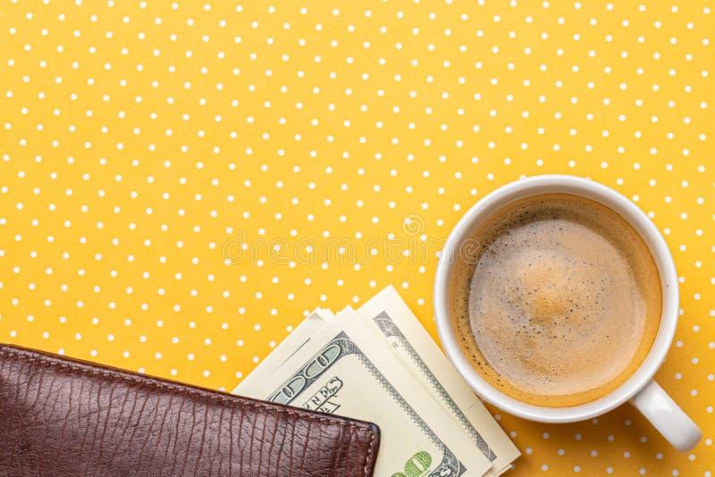 Vista superior de uma xícara de café e de uma pilha de notas de dólar em uma bolsa fotografia de stock