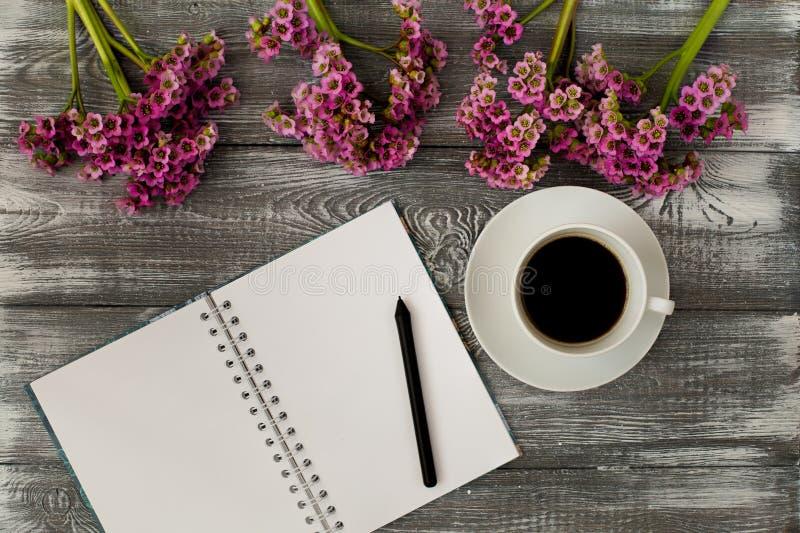 Vista superior de un diario o un cuaderno, lápiz y café y una flor púrpura en una tabla de madera gris Diseño plano imagenes de archivo