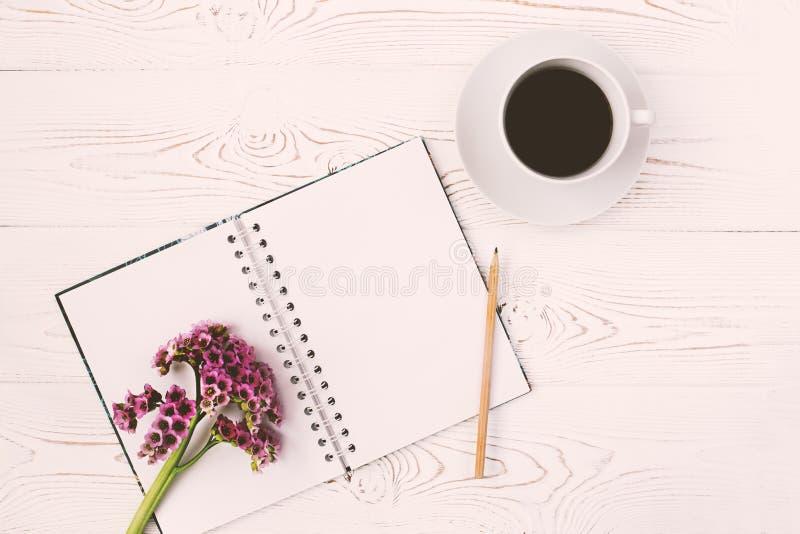 Vista superior de un diario o un cuaderno, lápiz y taza de café y de una flor púrpura en una tabla de madera blanca Dise?o plano fotos de archivo