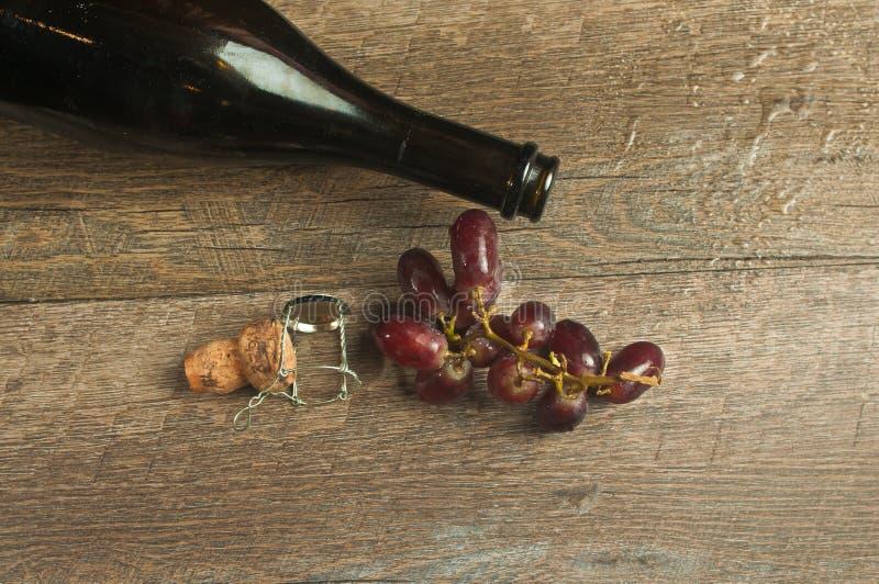 Vista superior de una botella vacía de chamán francés con el corcho y las uvas imagenes de archivo