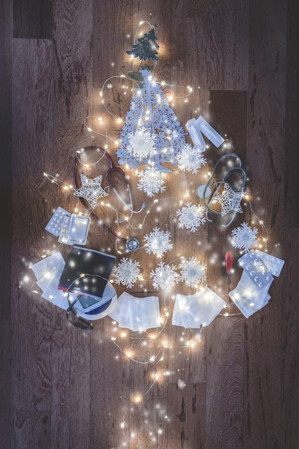 Vista superior de una composición del equipamiento médico en forma de un árbol de navidad y de luces en fondo de madera La Navida imágenes de archivo libres de regalías