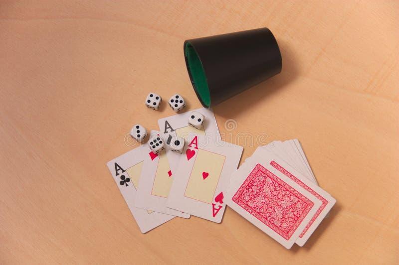 Vista superior de una cubierta de tarjetas y de dados en una tabla de madera ligera imagen de archivo