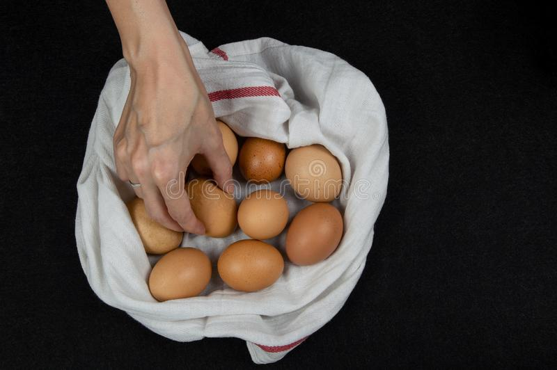 Vista superior de una mano femenina que escoge el huevo fresco de un paño blanco en un tablero de la mesa imagenes de archivo