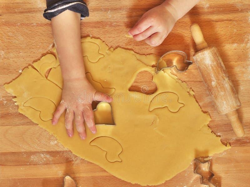Vista superior de una pequeña mano de los niños usando el cortador de la galleta imágenes de archivo libres de regalías