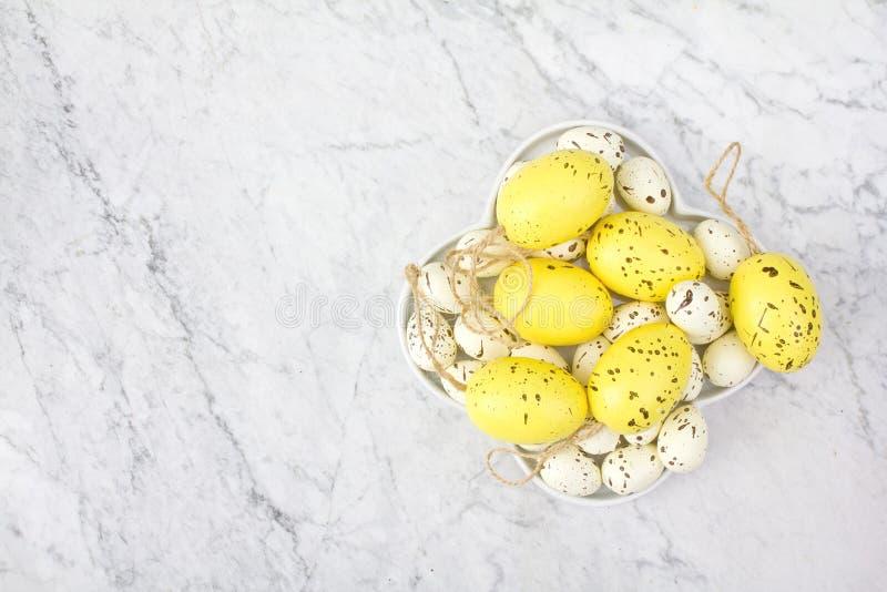 Vista superior de una placa blanca con los huevos de codornices amarillos e imitados de las motas en el fondo de mármol fotografía de archivo