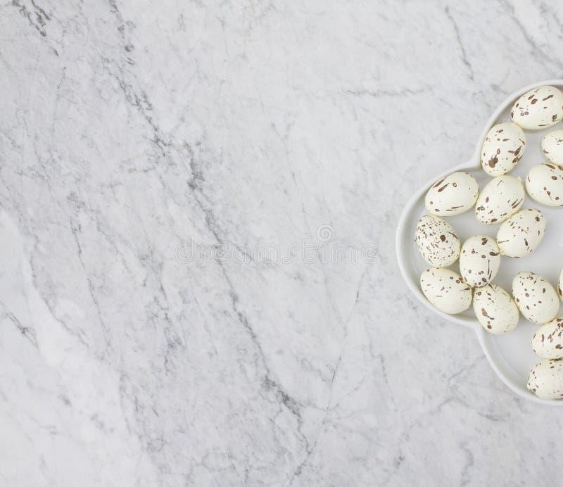 Vista superior de una placa medio blanca con los huevos de codornices imitados de las motas en el fondo de mármol foto de archivo