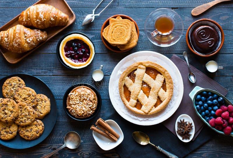 Vista superior de una tabla de madera por completo de tortas, frutas, café, galletas imagen de archivo