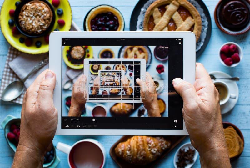 Vista superior de una tabla de madera por completo de tortas, frutas, café, galletas fotos de archivo libres de regalías