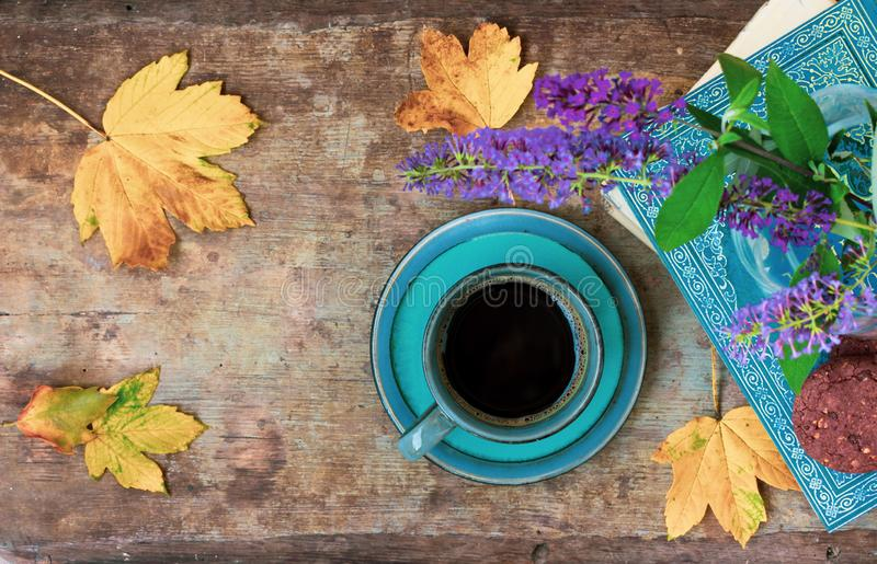 Vista superior de una taza azul de café, de libro, de flores, de galletas y de hojas en fondo de madera fotografía de archivo