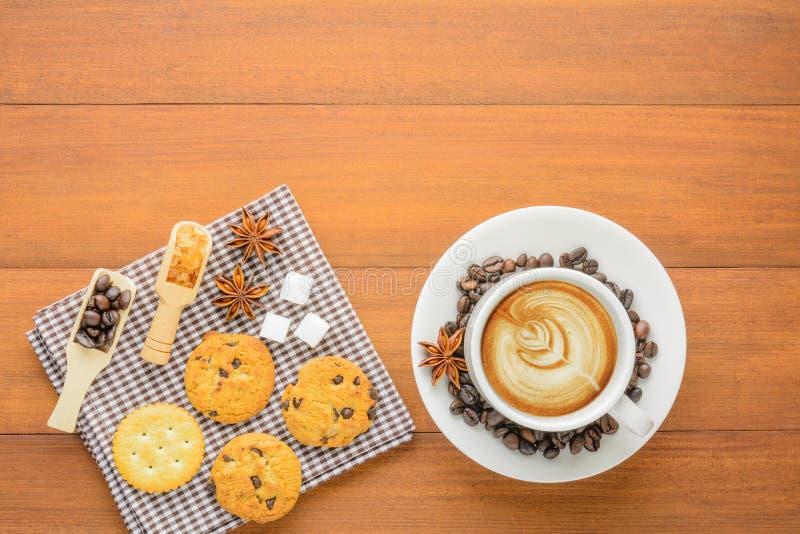 Vista superior de una taza de café con las galletas y las galletas en la madera TA imagen de archivo