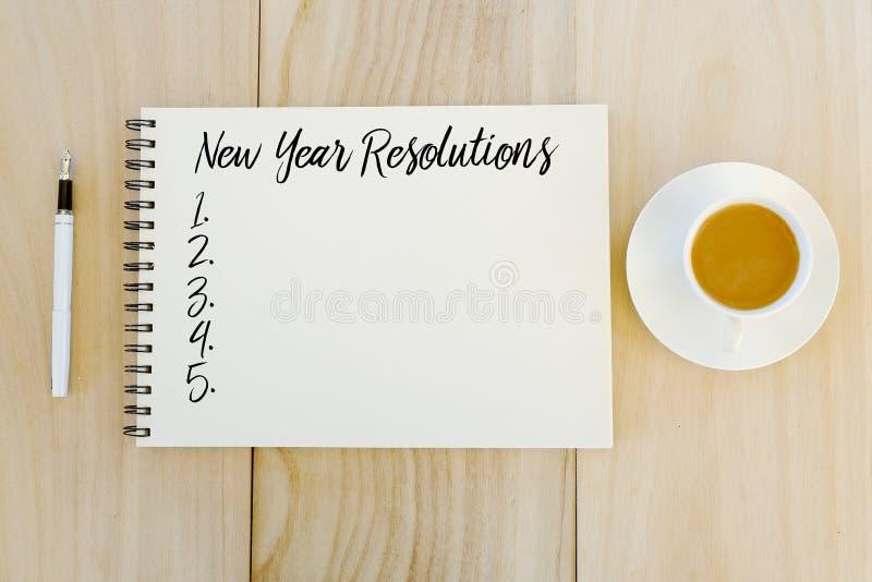 Vista superior de una taza de café, de pluma y de cuaderno escritos con resoluciones del Año Nuevo en fondo de madera fotos de archivo libres de regalías