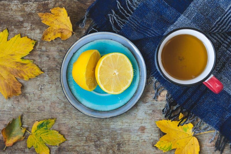 Vista superior de una taza de té, de bufanda azul, de limón cortado y de hojas en fondo de madera foto de archivo libre de regalías