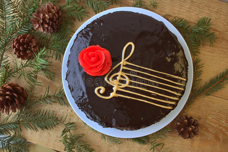 Vista superior de una torta de chocolate con una imagen estilizada de un personal musical Stave With una G-clave y un fondo de ma imagen de archivo libre de regalías